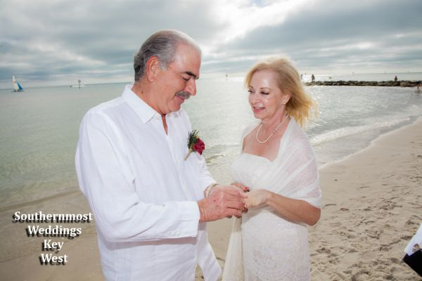 Wedding couple exchange rings next to the ocean during their wedding ceremony by Southernmost Weddings Key West