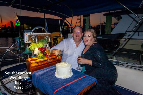 Wedding couple cuts their wedding cake during their sunset sail reception planned by Southernmost Weddings Key West