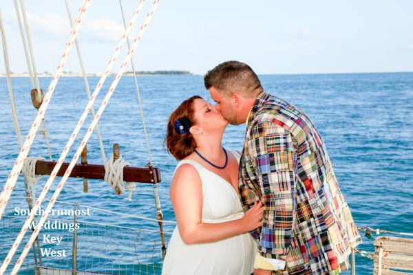 Wedding couple kisses after getting married by Southernmost Weddings on a private old-fashion Schooner sailboat wedding