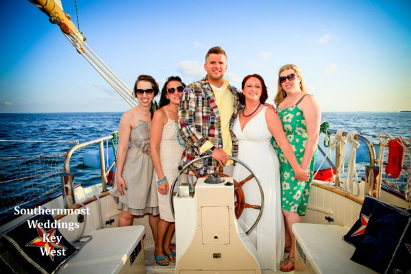 Wedding party pose for photos during their private sunset sailboat reception by Southernmost Weddings