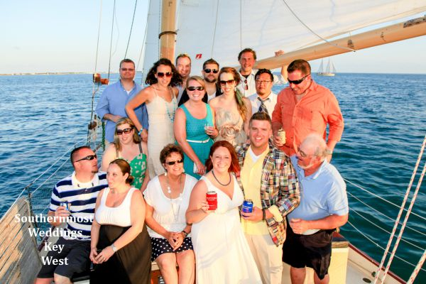 Wedding party pose for photos during their private sunset sailboat wedding planned by Southernmost Weddings Key West