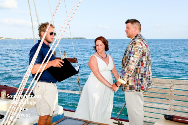 The Captain performs a ceremony during a private sunset sailboat wedding off the coast of Key West, Florida by Southernmost Weddings