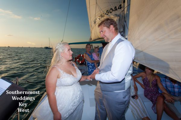 Wedding couple exchange vows during their private sunset sailboat wedding by Southernmost Weddings