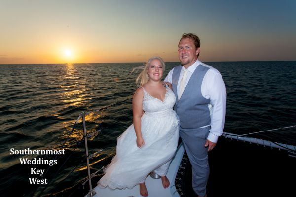 Wedding couple pose for photos by Southernmost Weddings with the sunset in the background