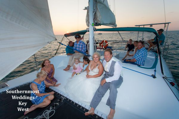 Wedding couple relax on the bow of their private catamaran sunset sail during their reception by Southernmost Weddings