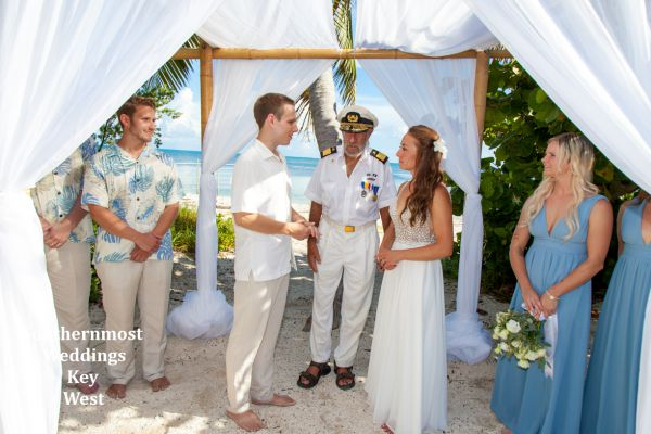 Wedding couple getting married under a bamboo wedding arch next to the ocean.