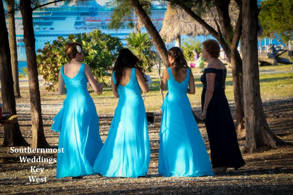 Bridesmaids wait under some shady pine tree while waiting for the wedding to start.
