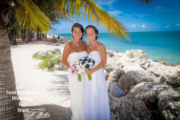 Two Brides poses under a shady palm tree after their wedding