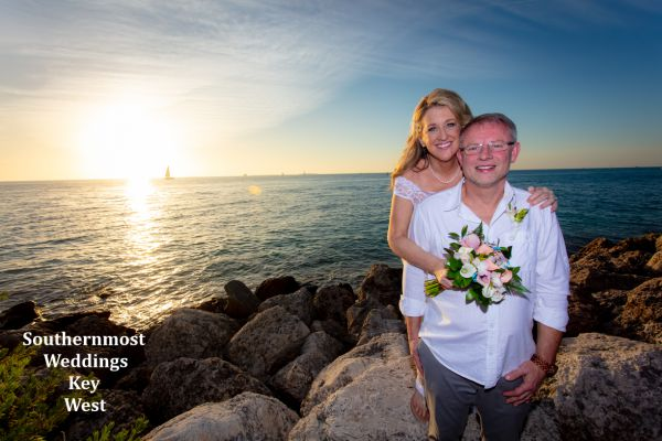 Wedding couple pose for photos by Southernmost Weddings overlooking the Gulf of Mexico at sunset