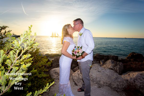 Bride & Groom pose for photos in front of the setting sun after there wedding by Southernmost Weddings Key West