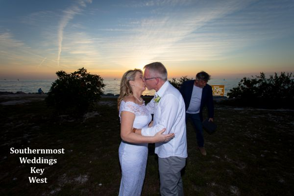 Wedding couple kisses in front of the setting sun after their wedding planned by Southernmost Weddings Key West