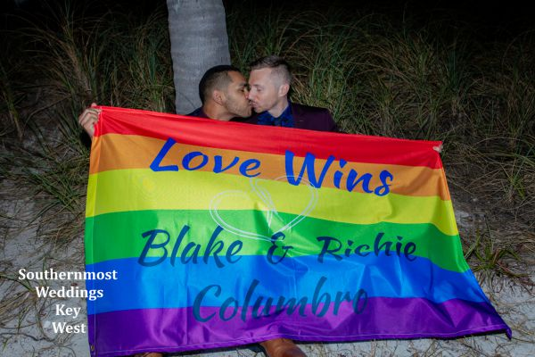 Two men kiss under a rainbow flag after their wedding y Southernmost Weddings Key West