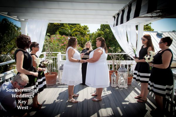 Two ladies exchange wedding vows on the rooftop of their Key West Guesthouse