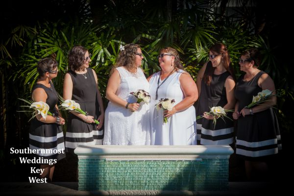 Wedding party poses for photos by the pool after their wedding by Southernmost Weddings Key West