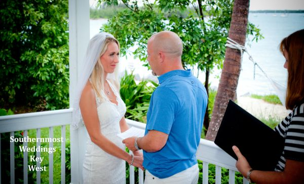 Wedding officiant marries a couple on their guesthouse porch. Image by Southernmost Weddings