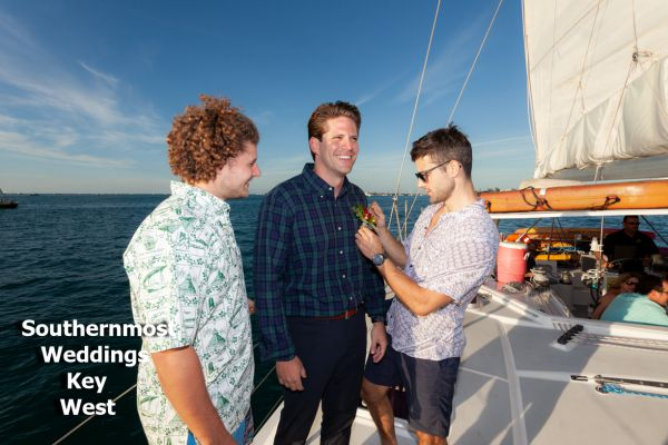 Groomsmen pose for photos during a private sunset sailboat wedding by Southernmost Weddings