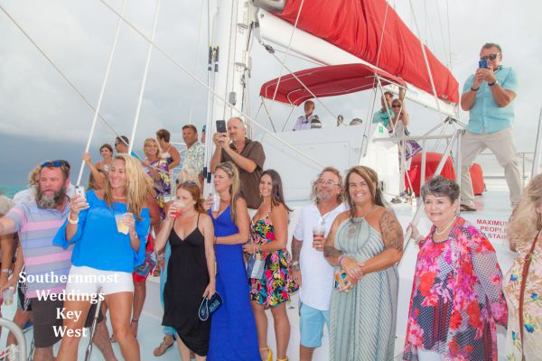 Wedding party pose for photos during their private sunset sailboat reception planned by Southernmost Weddings Key West
