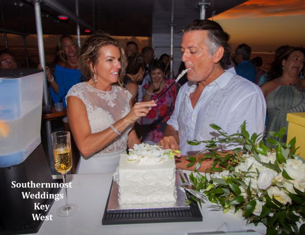 Bride & Groom enjoy some wedding cake after their wedding by Southernmost Weddings Key West