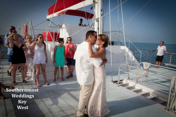 Wedding couple dances on the deck of a large stable catamaran during their sunset sail wedding reception