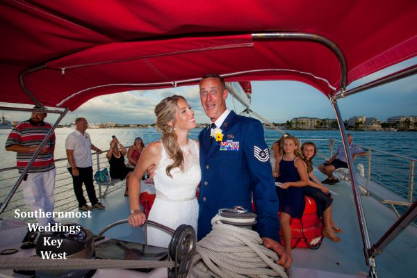 Wedding couple steering the sailboat during their private sunset sail wedding cruise planned by Southernmost Weddings Key West