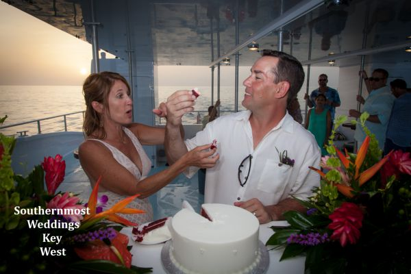 Bride & Groom cut the wedding cake during their private sunset sail reception planned by Southernmost Weddings Key West