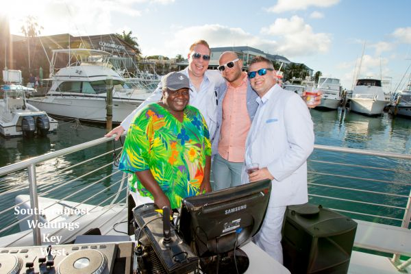 Wedding party hangs with the DJ during their sunset sail reception planned by Southernmost Wedding Key West