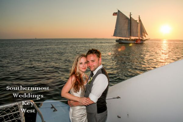 Bride & Groom stand in front of the setting sun on their private sunset sail after their wedding by Southernmost Weddings Key West