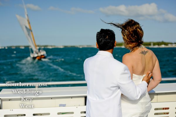Bride & Groom pose for photos in front of an old-fashioned historic Schooner after their wedding by Southernmost Weddings Key West