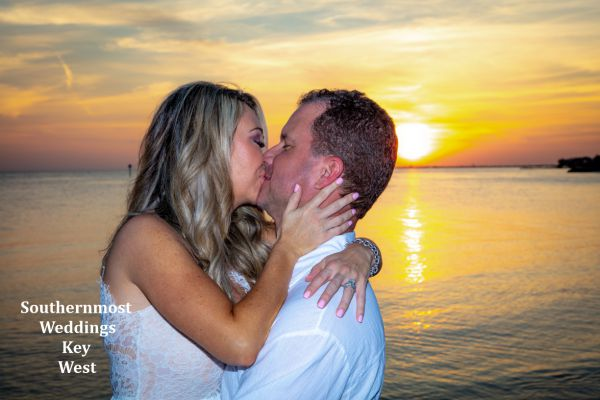 Bride & Groom stand in front of the setting sun for photos after their wedding by Southernmost Weddings Key West