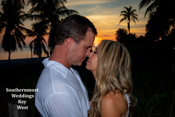 Wedding couple pose for photos on Smathers Beach after their wedding by Southernmost Weddings with the sunset in the background