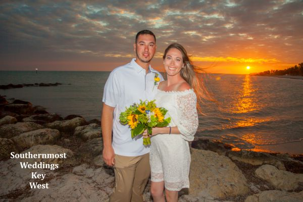 Wedding couple takes pictures in front of the setting sun after getting married by Southernmost Weddings Key West on Smathers Beach