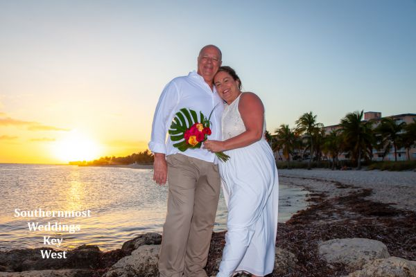 Wedding couple next to the Atlantic Ocean after getting married at sunset on Smathers Beach in Key West, Florida