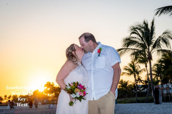 Wedding couple pose for photos during their sandy sunset beach wedding by Southernmost Weddings