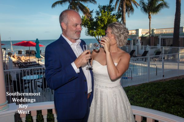 Wedding couple drink champagne at the Southernmost House before their  wedding by Southernmost Weddings