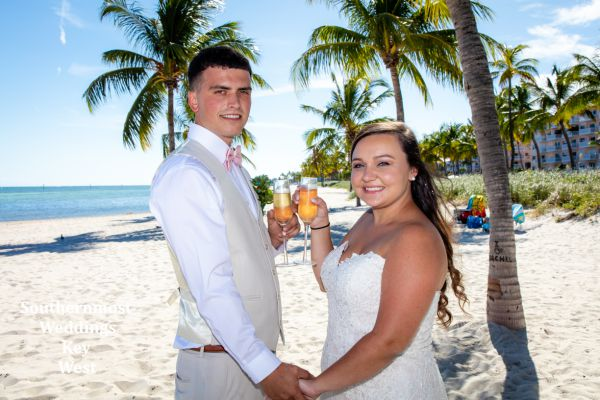 Wedding couple toast champagne after their barefoot Beach Wedding by Southernmost Weddings