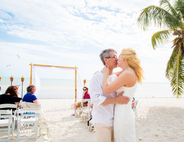 Wedding couple kisses after being married by Southernmost Weddings Key West on Smathers Beach
