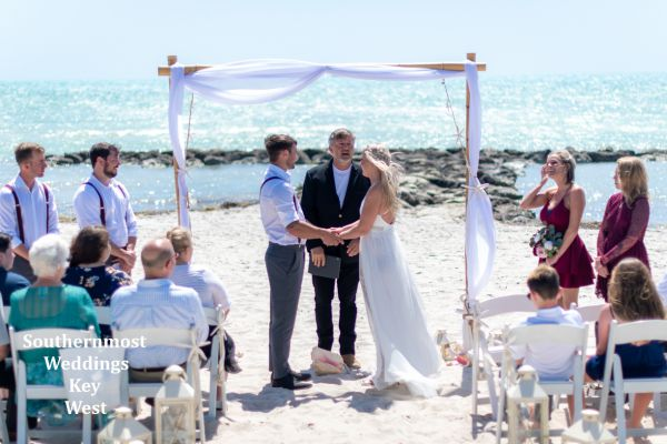 Wedding couple marring under a Bamboo Arch on Smathers Beach in Key West, Florida