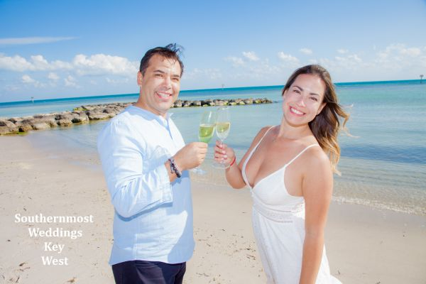 Wedding couple celebrate their wedding by Southernmost Weddings Key West with a Champagne Toast  on Smathers Beach