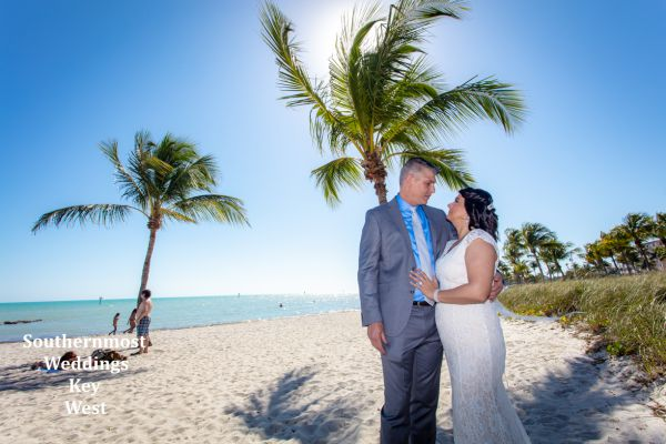 Wedding couple pose under a palm tree on Smathers Beach