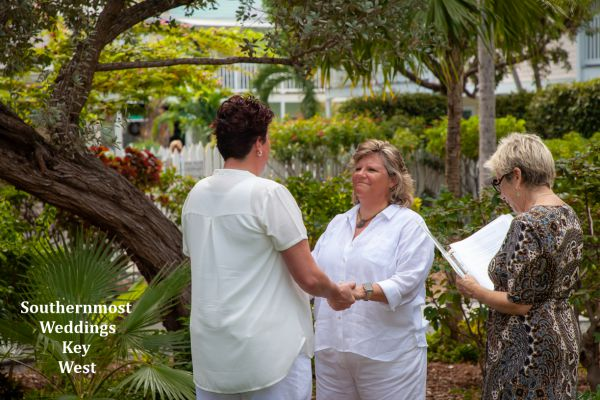Two ladies exchange wedding vows in the Truman Annex Butterfly Garden