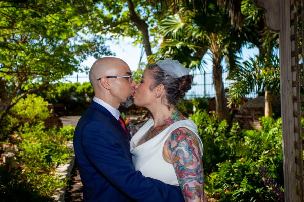 Wedding couple kiss in a historic tropical garden after their wedding planned by Southernmost Weddings Key West