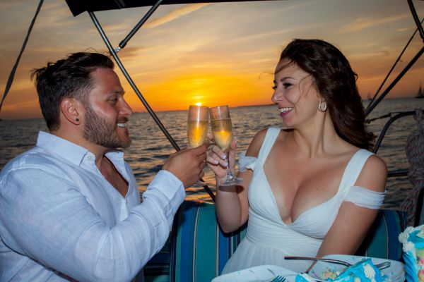 Bride & Groom celebrate their new life together with a glass of champange on their private sunset sailboat wedding planned by Southernmost Weddings