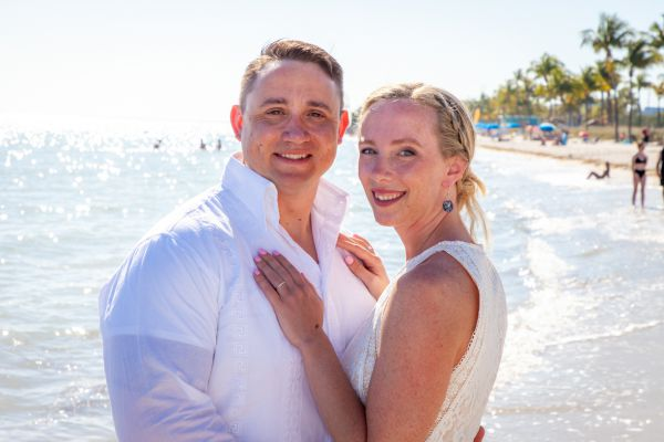 Bride & Groom pose for photos next to the ocean following their romantic beach elopement planned by Southernmost Weddings
