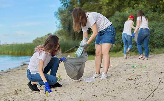 picture of people picking up trash on a beach
