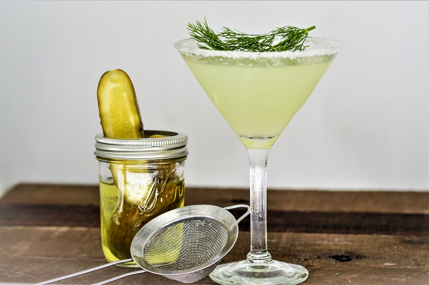 Dill Pickle Martini with jar of pickles and cocktail strainer