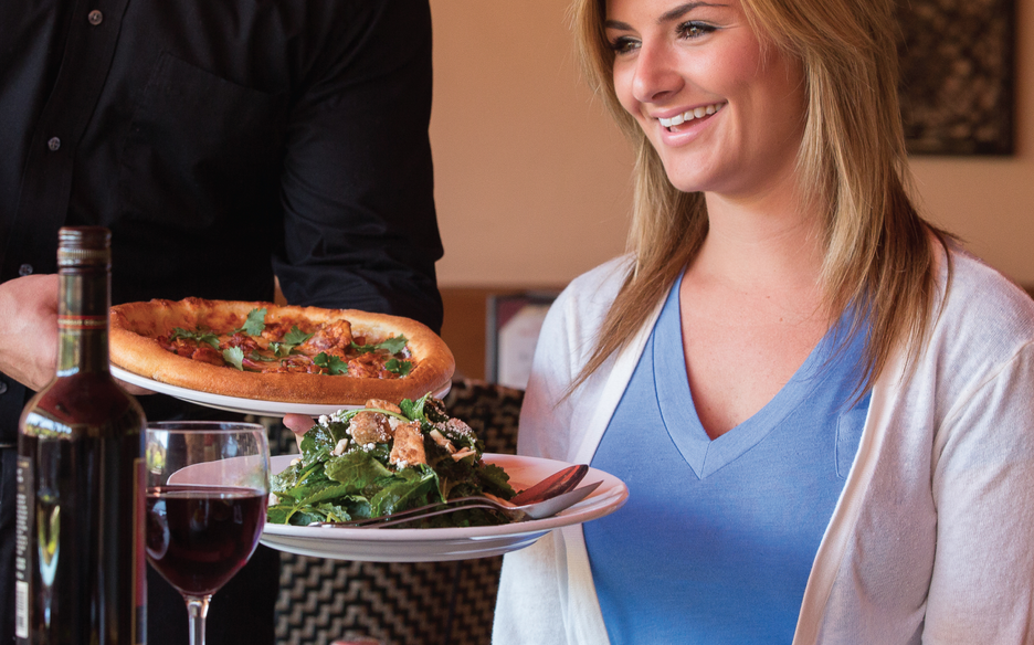 Lady being served pizza and salad