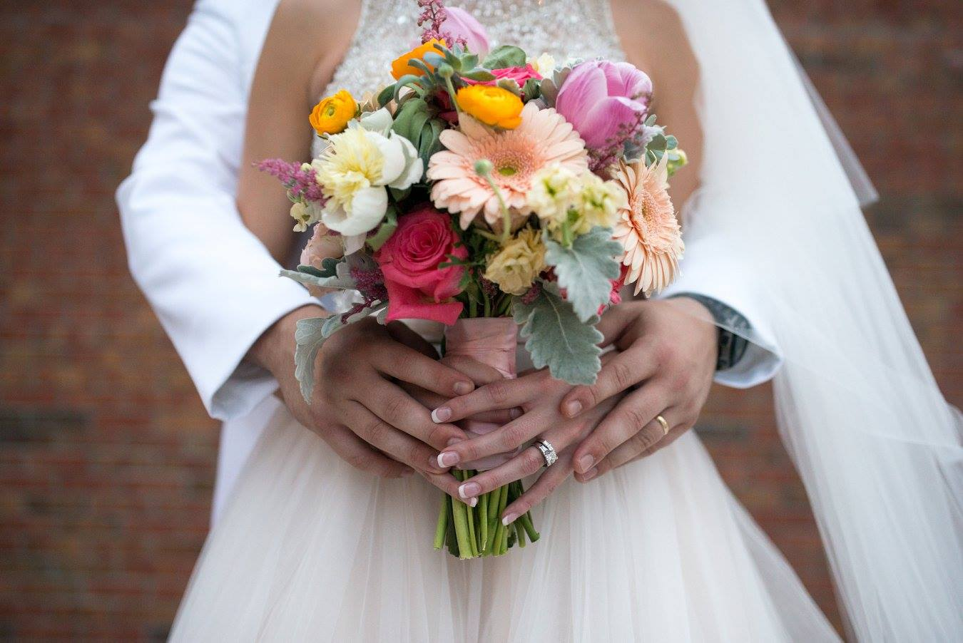 Couple holding hands over Bouquet