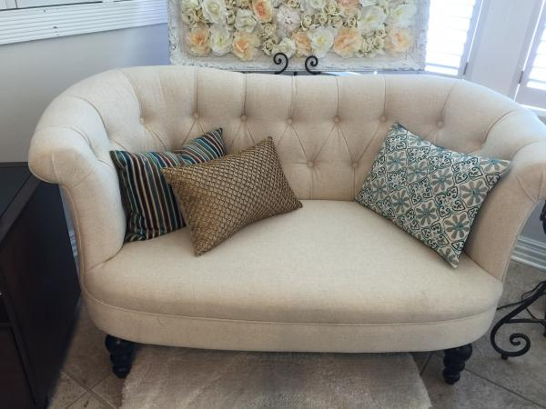 Tufted cream-colored couch with decorative pillows