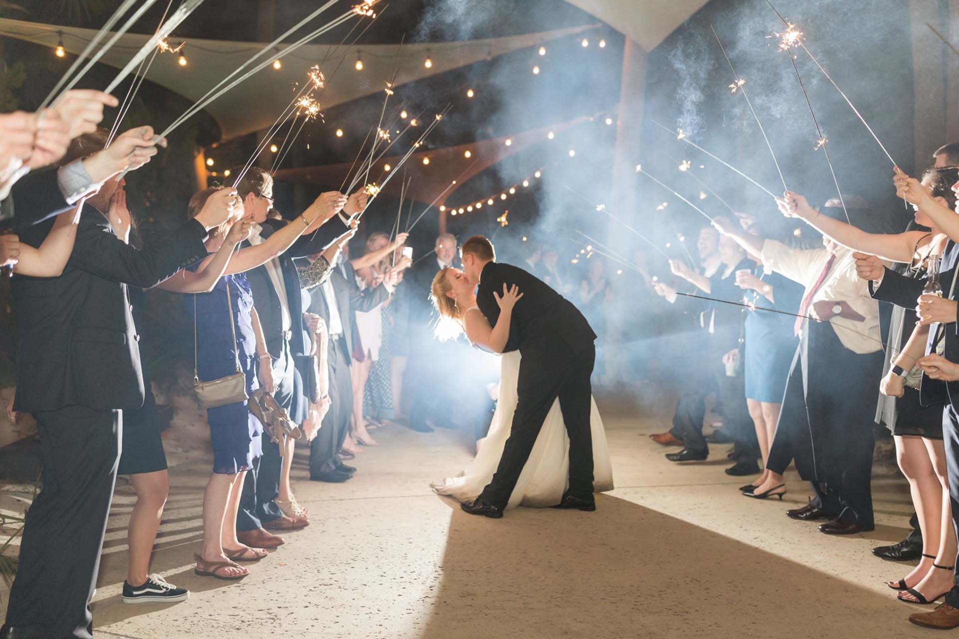 Bride and groom with guests holding sparklers