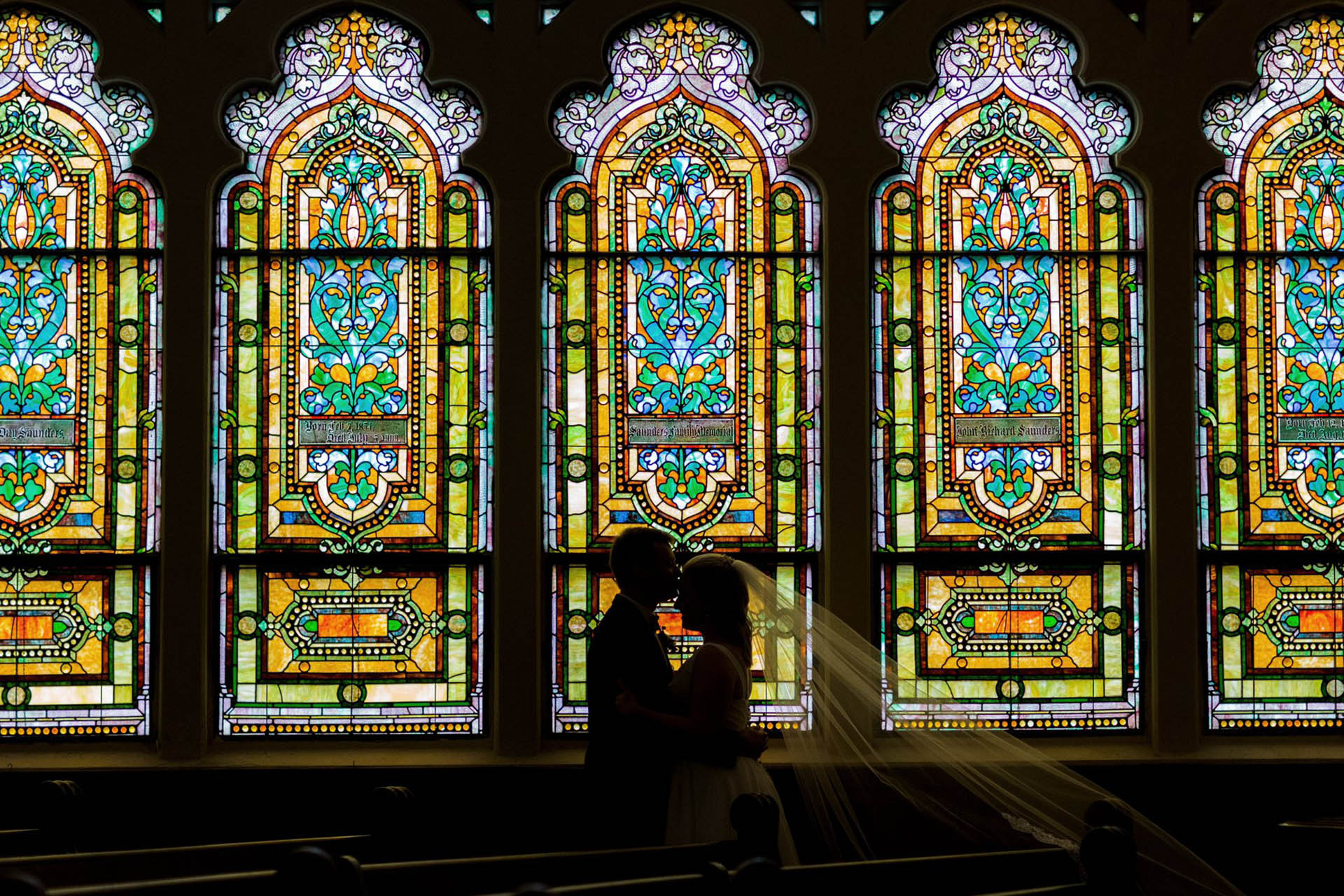 Bride and groom kissing in front of stained glass windows